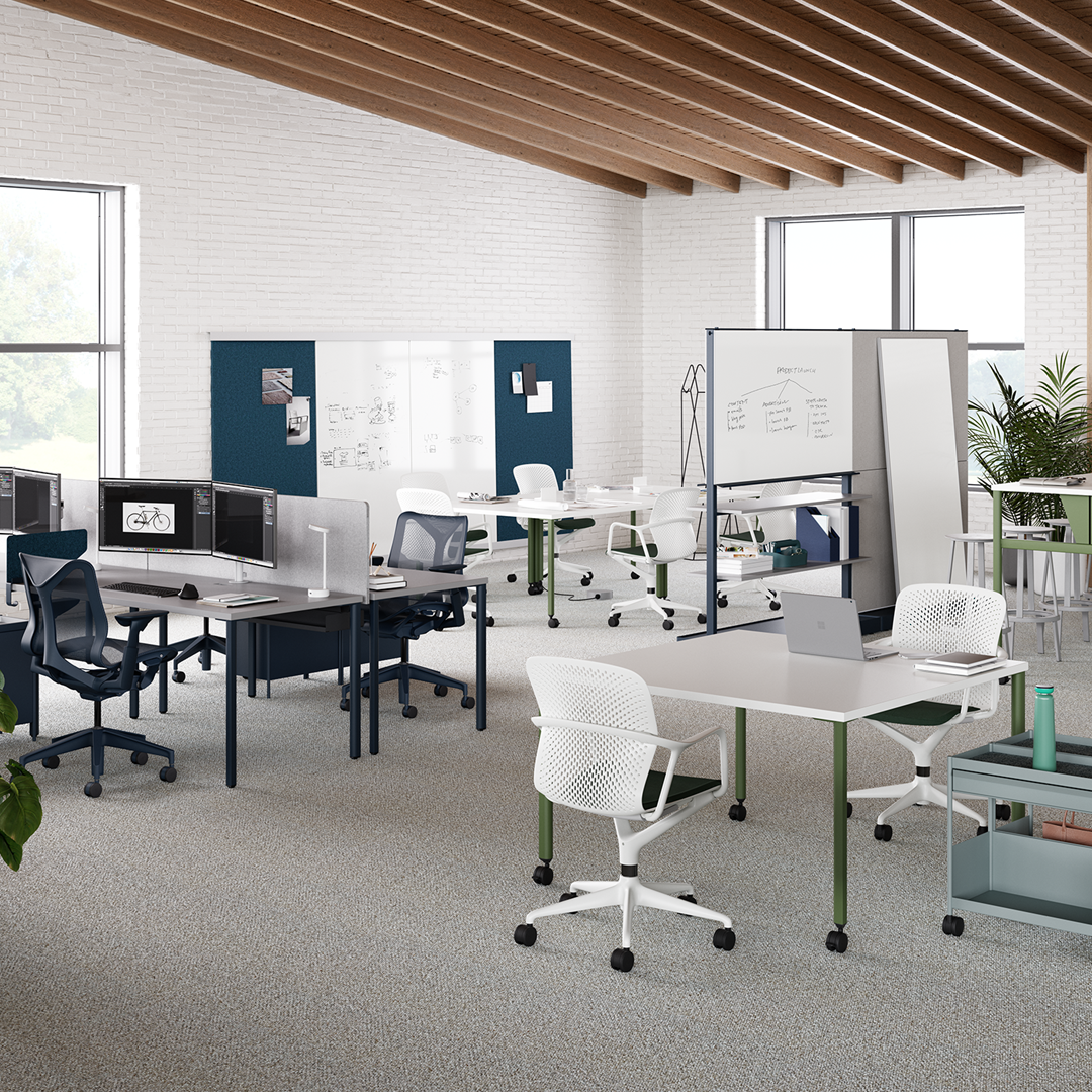 An office setting with white Caper chairs surrounding an OE1 Rectangular Table with a white top and sage green legs on casters with workstations beyond.