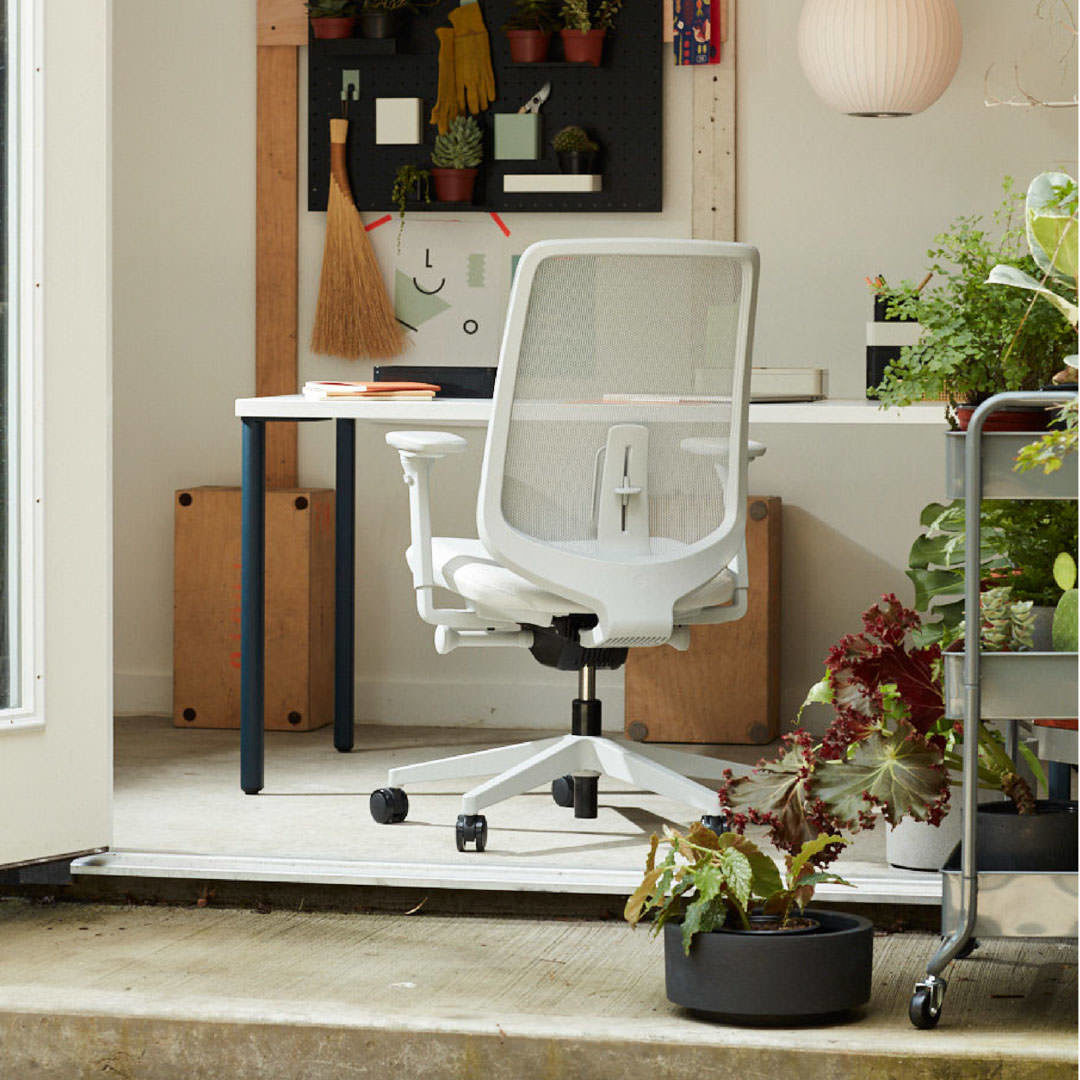 A home office with a light grey Verus task chair in front of an OE1 Rectangular Desk with a white top and navy legs surrounded by plants and art,