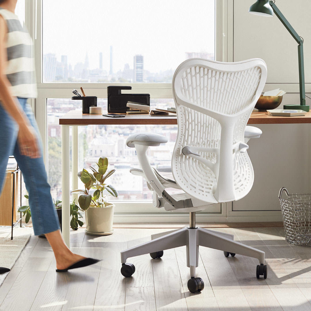 A white Mirra task chair in front of a walnut and white OE1 Desk with the silhouette of a woman walking past.