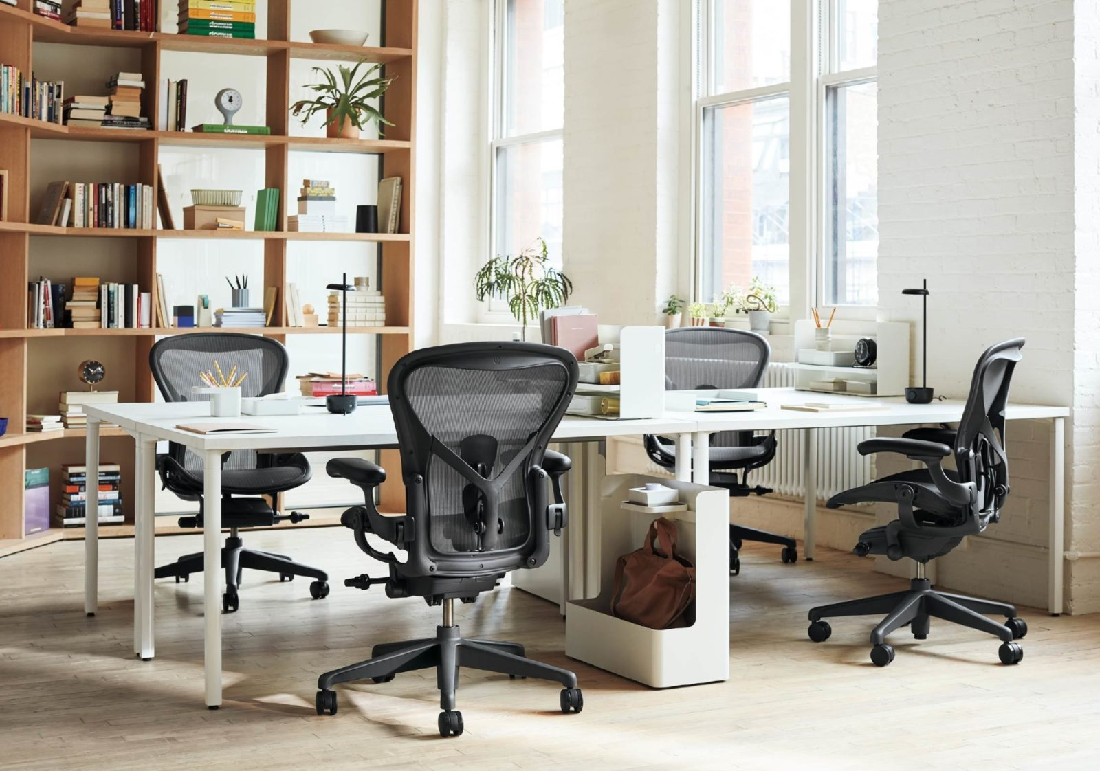 Black Aeron chairs at white OE1 Rectangular Desks with Ubi Work Tools and other desk accessories in a light-filled office.