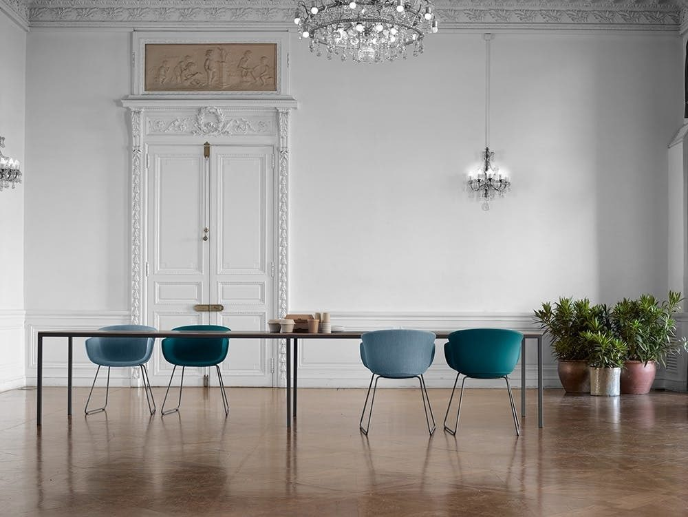 A long wood conference table surrounded by upholstered grey and blue guest chairs in a room with a wood floor and glass chandelier.