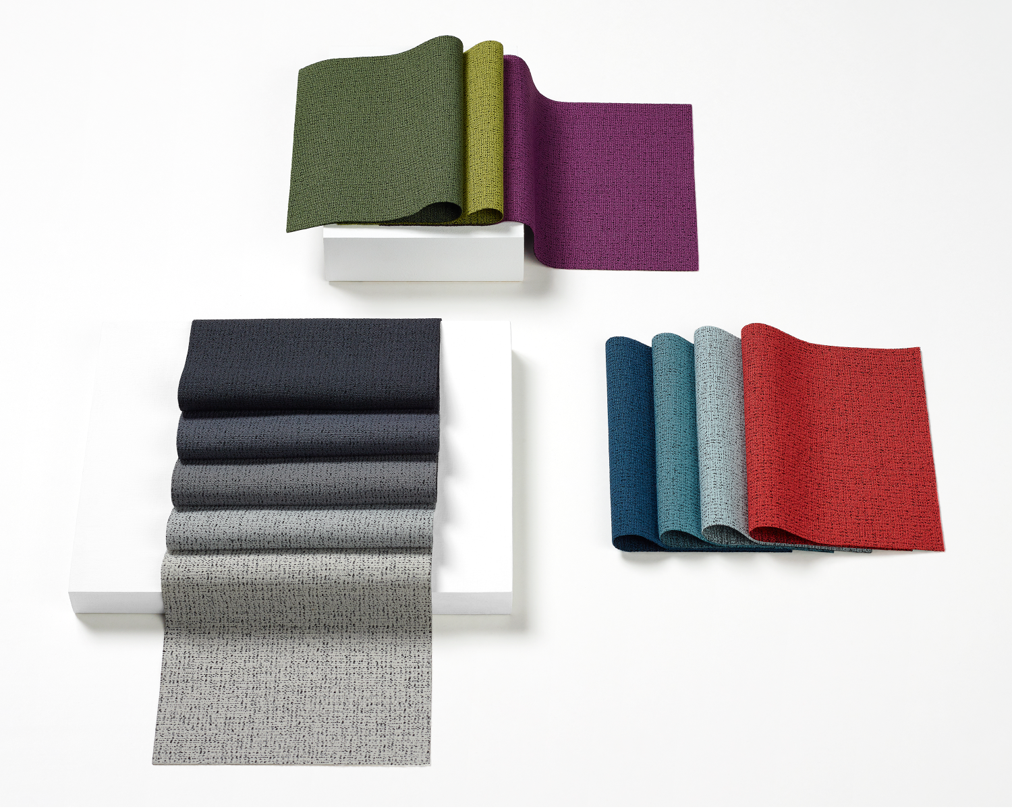 An image of Scatter fabric swatches on a white worksurface. Colors range from vibrant to neutral and include black, grey, green, purple, blue, and red.