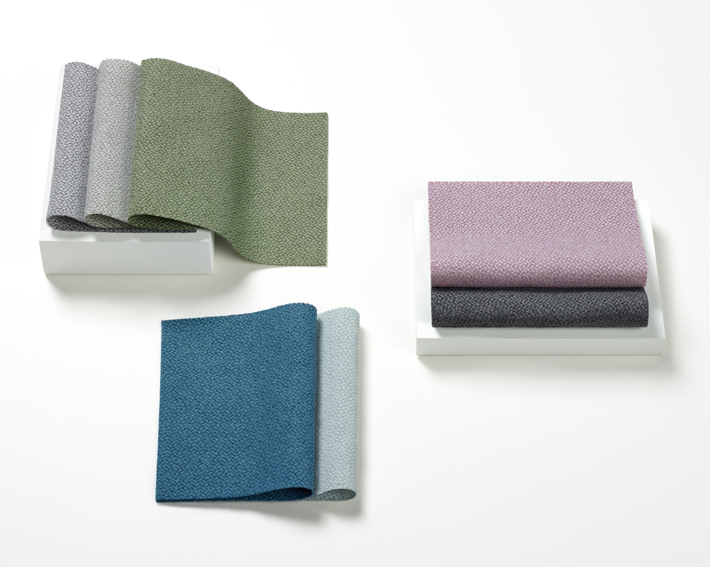 An image of Mellow fabric swatches on a white surface. Colors are cool and include blues, purples, greens, and greys.