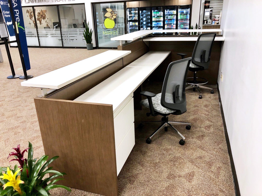 A Verus Chair and Verus Stool behind a wood information desk with laminate countertops.