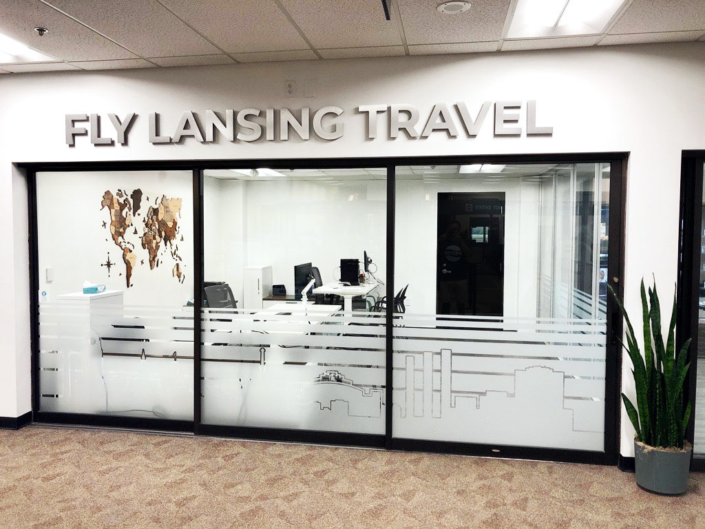 """A hallway in the airport with a glass interior wall covered in decorative glazing below metal letters spelling """"Fly Lansing Travel"""""""