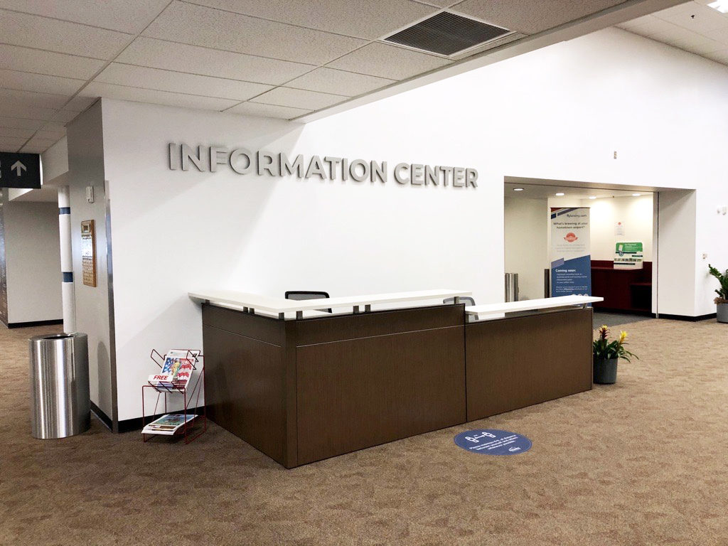 """A wood information desk with a white laminate top with the words """"Information Center"""" on the wall above it."""
