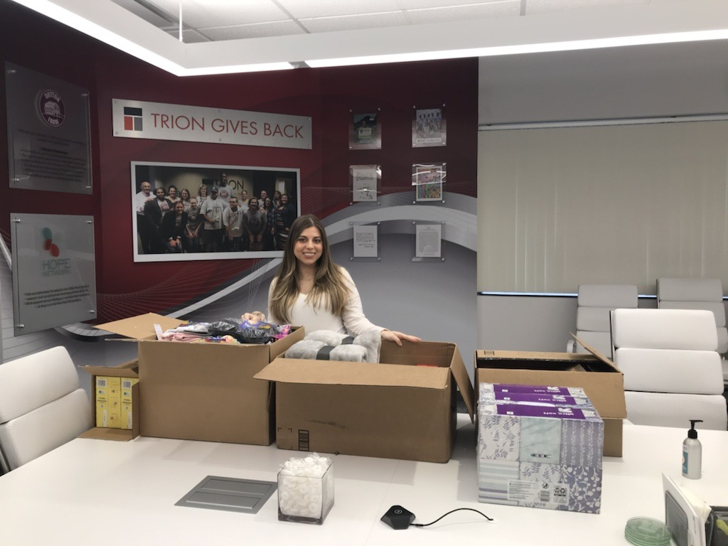 An image of a woman in the Trion Solutions office packing boxes of donations.