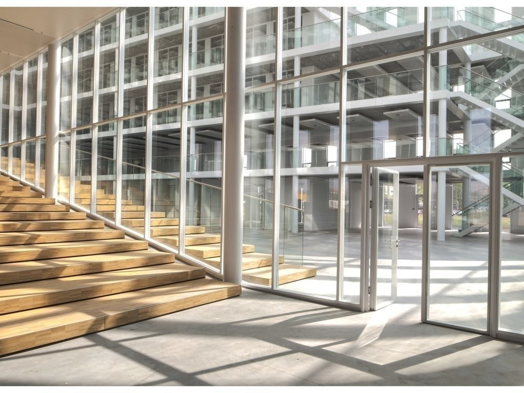A lobby with white metal and glass Maars String2 Walls next to wooden stairs.