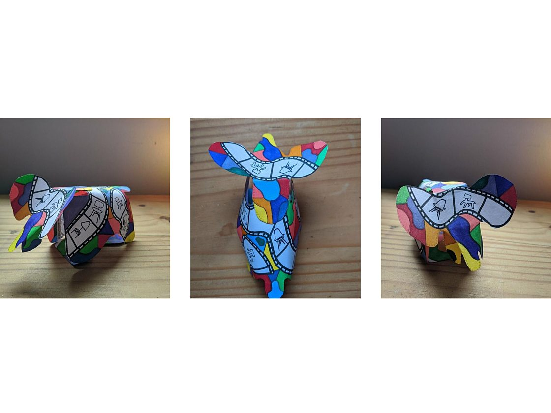 Three images of a three dimensional paper elephant from different angles decorated in with bright colored patterns and hand-drawn images of Eames chairs.