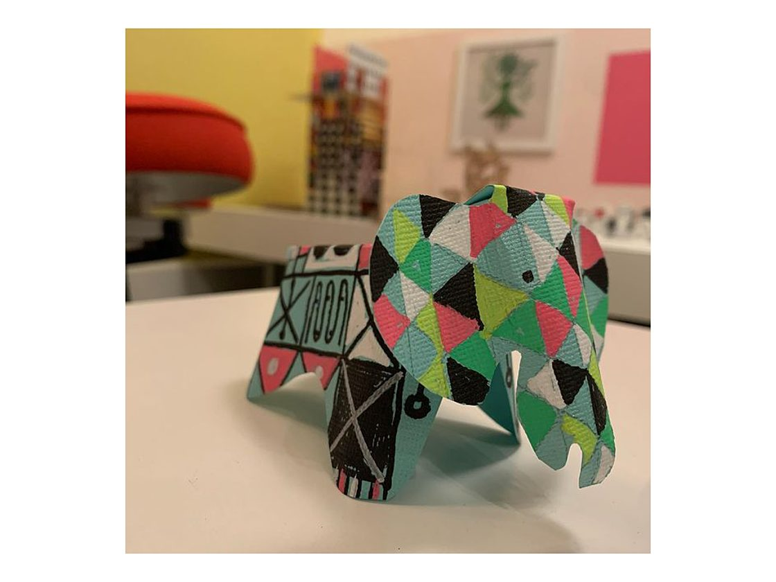 An image of a three dimensional paper elephant decorated with multi-colored triangles that form a geometric pattern.