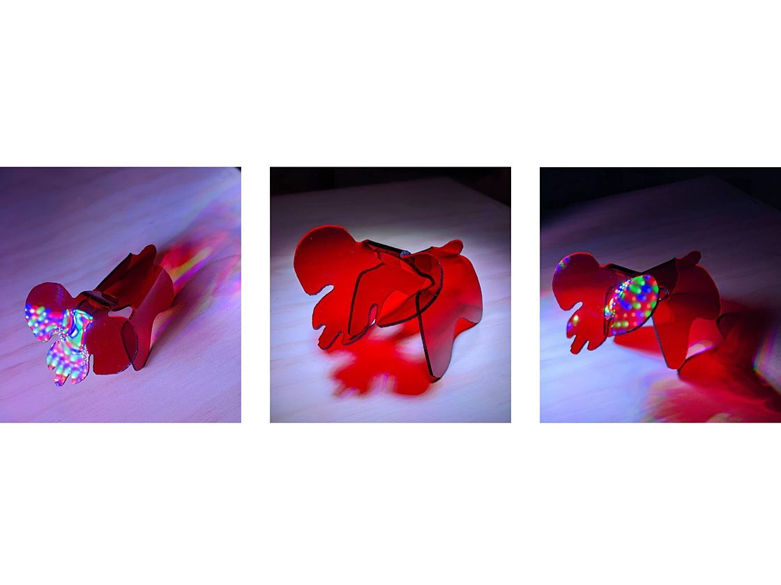 Three images of a three dimensional translucent red acrylic elephant from different angles with multicolored lights reflecting off it.