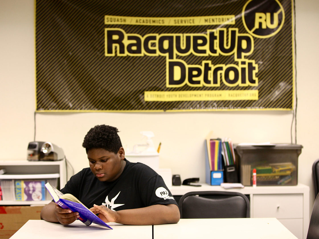 An image of a boy in a Racquet Up t-shirt reading a book at a desk in front of a Racquet Up banner.