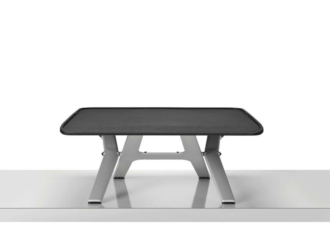 A Monto Sit-to-Stand Riser with a black top and silver legs on a silver surface in front of a white wall.