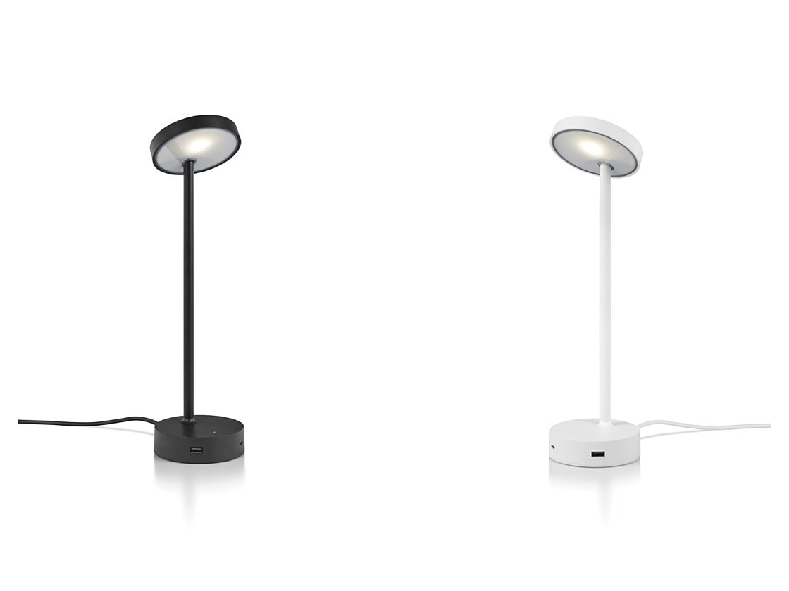 A lit up black CBS Lolly Personal Light facing a white Lolly lamp with a USB port showing.