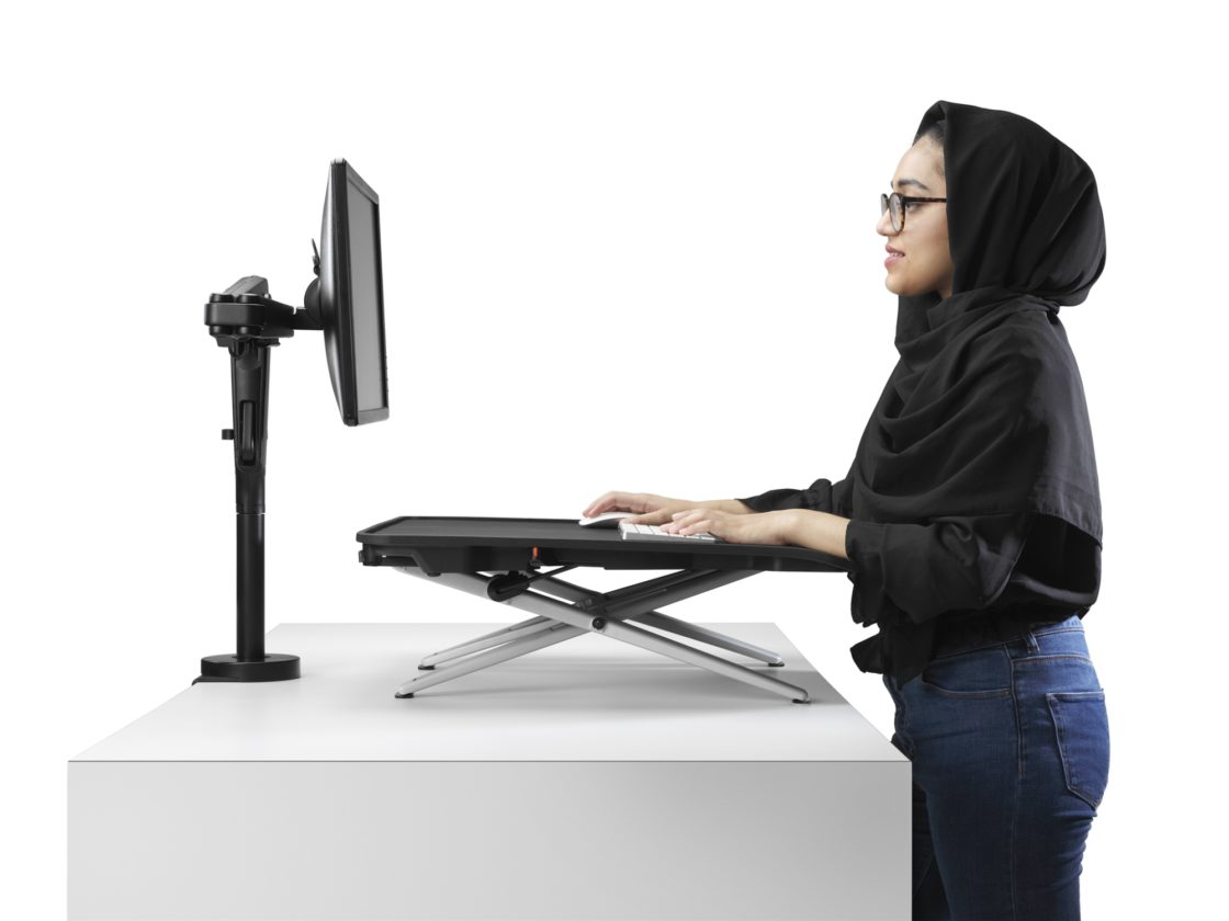 A woman standing at a white desk working on a keyboard set on top of a Monto Sit-Stand Desk looking at a screen mounted at eye level on an Ollin Arm.