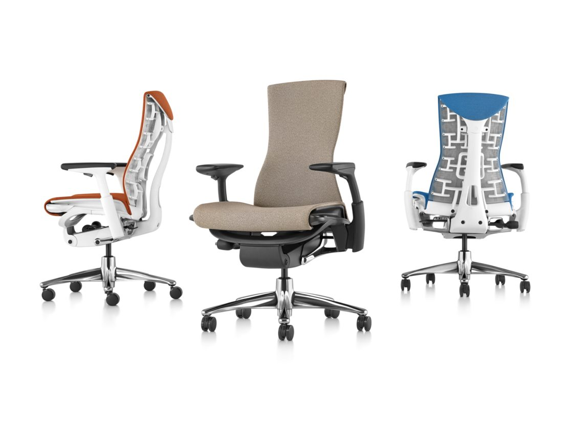 Three Embody chairs with different finishes facing sideways, forwards, and backwards to show off the ergonomic design.