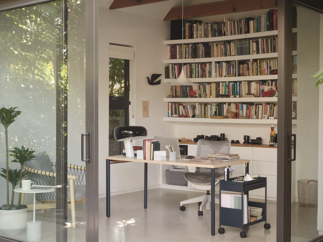 A home office with a navy OE1 Storage Trolley holding personal items in its open top and folders and books in its bottom shelf.
