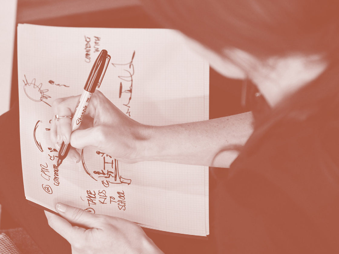 A photo of a woman drawing a diagram on paper.