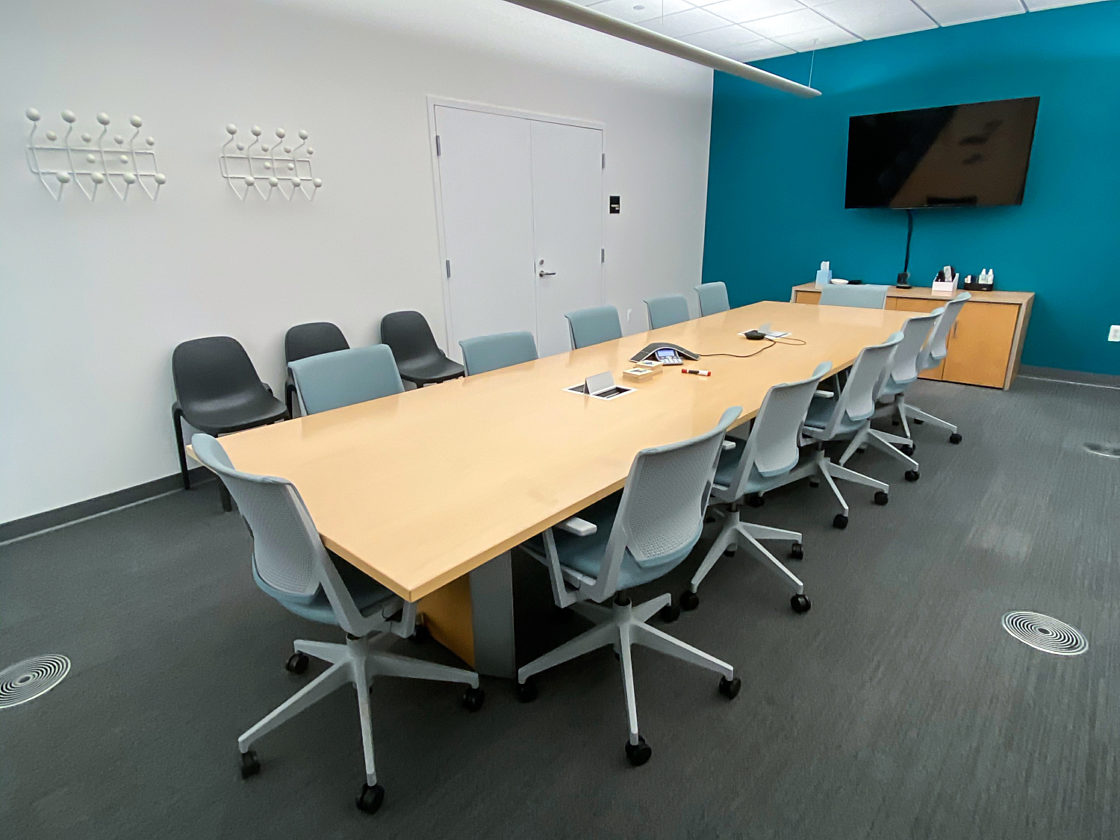 A long wood conference table surrounded by grey task chairs.
