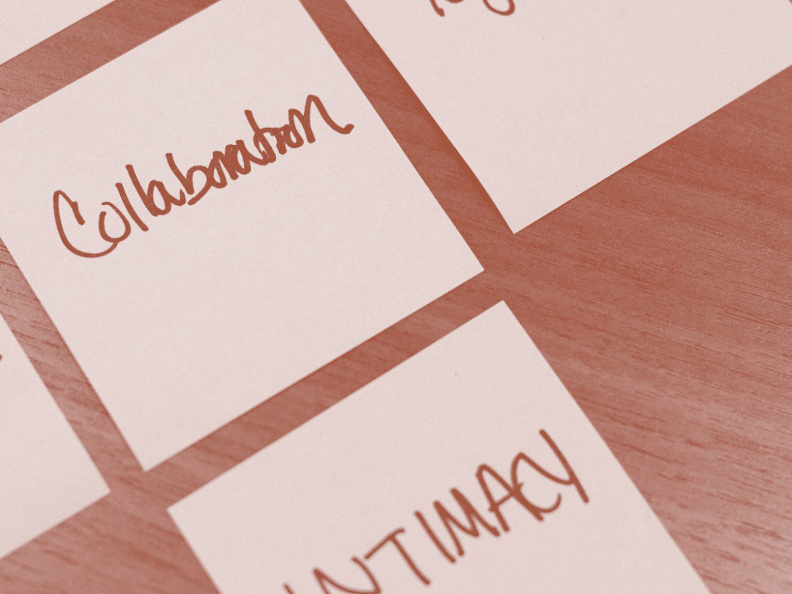 A photo of sticky notes grouped together that read collaboration, togetherness, and intimacy.