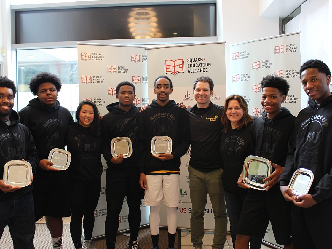 A group of kids and coaches in Racquet Up sweatshirts holding silver award plaques in front of a Squash Education Alliance banner.