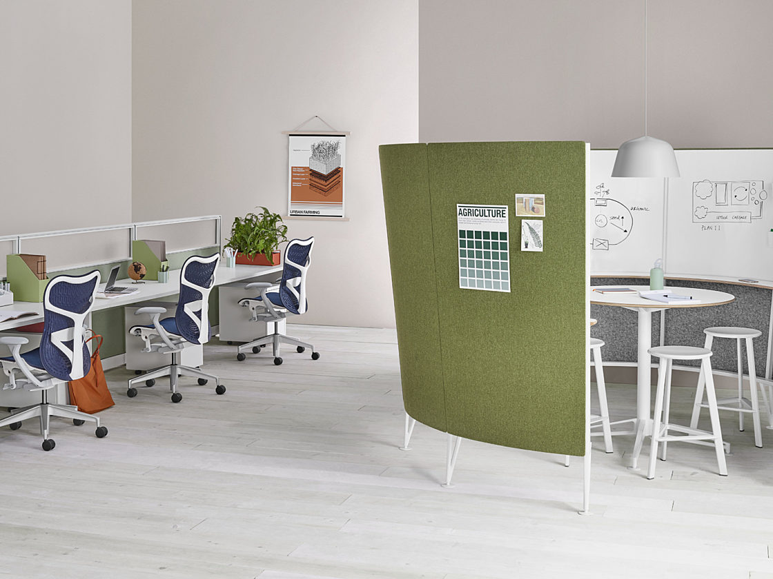 A semi-circular Prospect Creative Space with a green tackable fabric outside and a whiteboard inside with a white table and white stools inside.