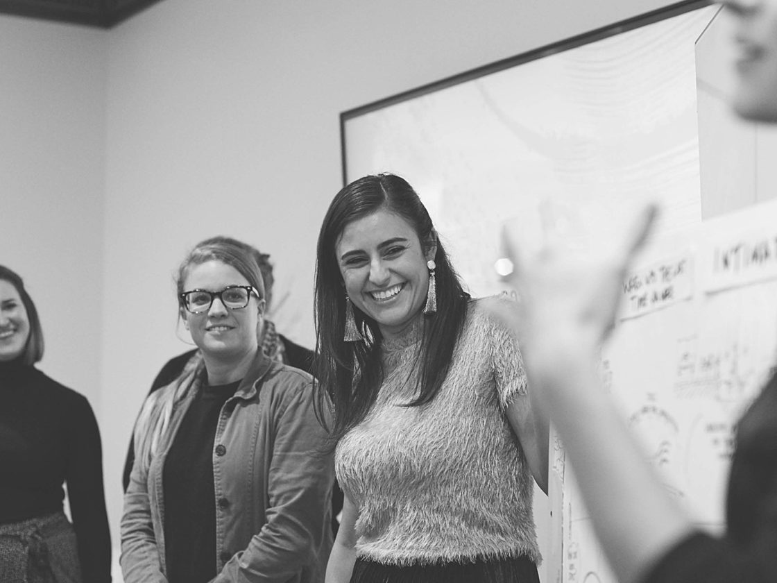 Three young women standing in front of a whiteboard smiling and listening to another woman speak.