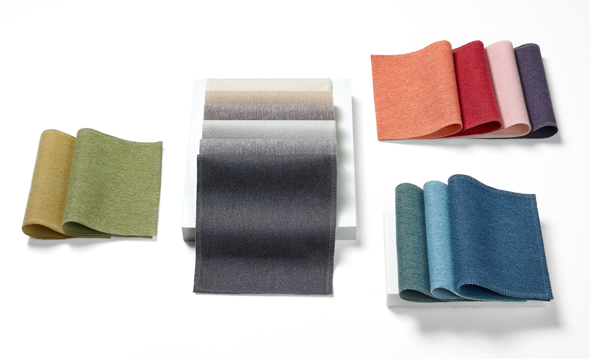 An image of Whisper fabric swatches on a white surface. Colors range from neutral to vibrant and include greens, blues, reds, and greys.