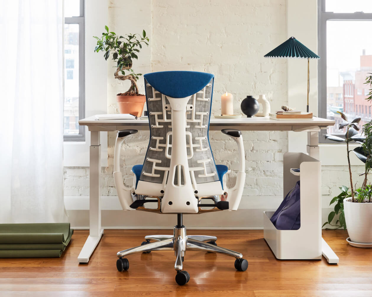 The back of an Embody chair with a white frame and blue upholstery in front of a sit-to-stand desk with Ubi Storage and a HAY table lamp in a home office.