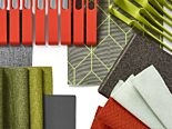 A swatch board with grey, green, and burnt orange fabrics and clips.