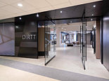 The entrance of DIRTT headquarters made of glass and metal partition walls with the DIRTT logo.