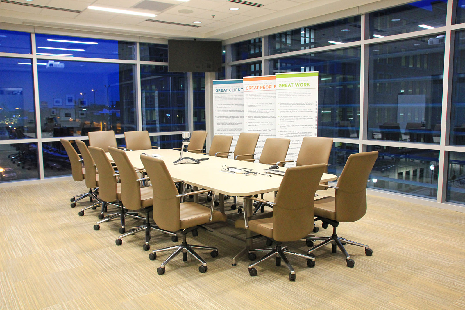 A glass-enclosed conference room with a long white conference table with inset power surrounded by high-back leather chairs.