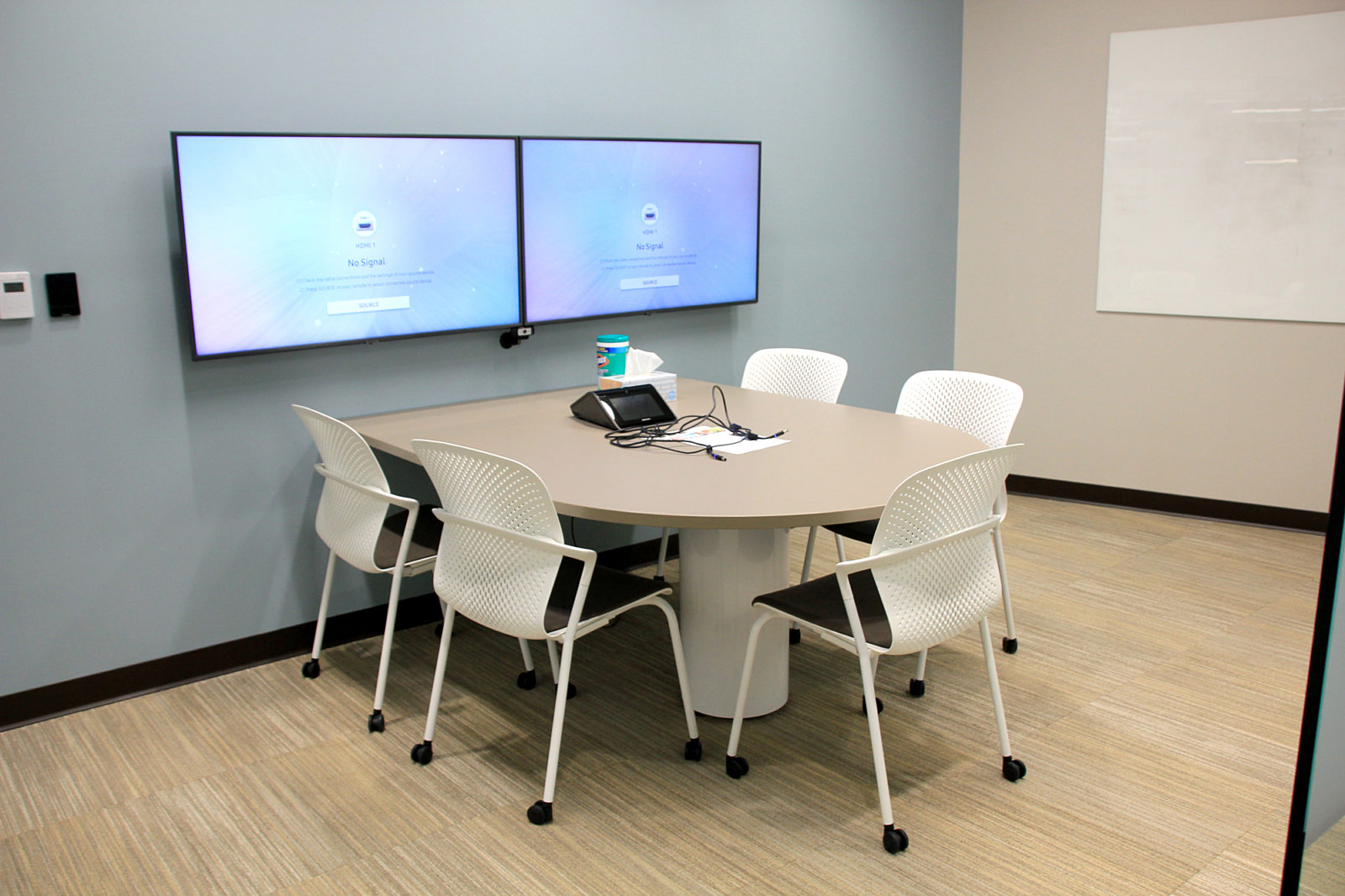 A D-Shaped table attached to a wall with two mounted TV screens surrounded by white mobile Caper chairs.