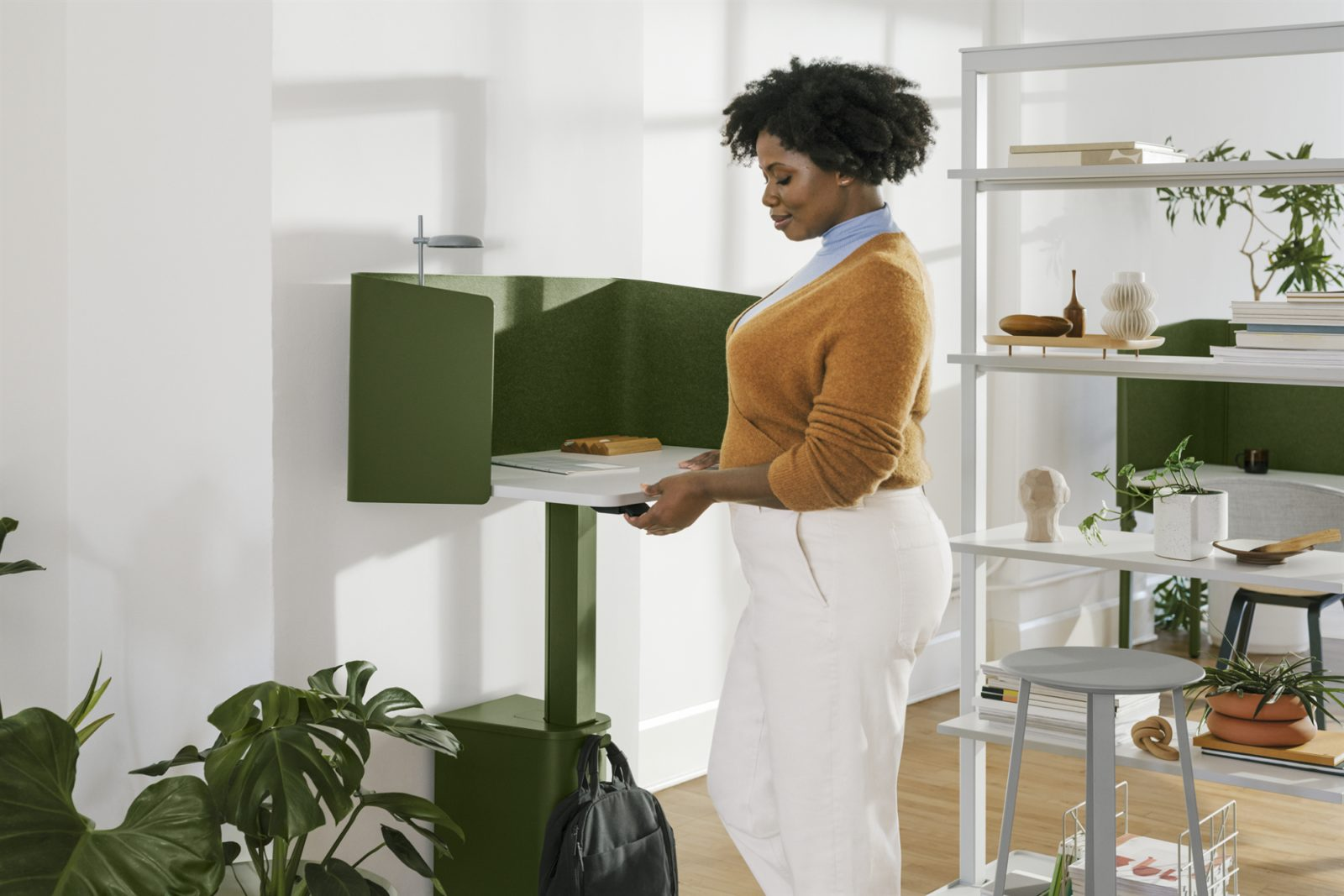 A person stands in front of a green OE1 Micropack adjusting the height of the work surface.