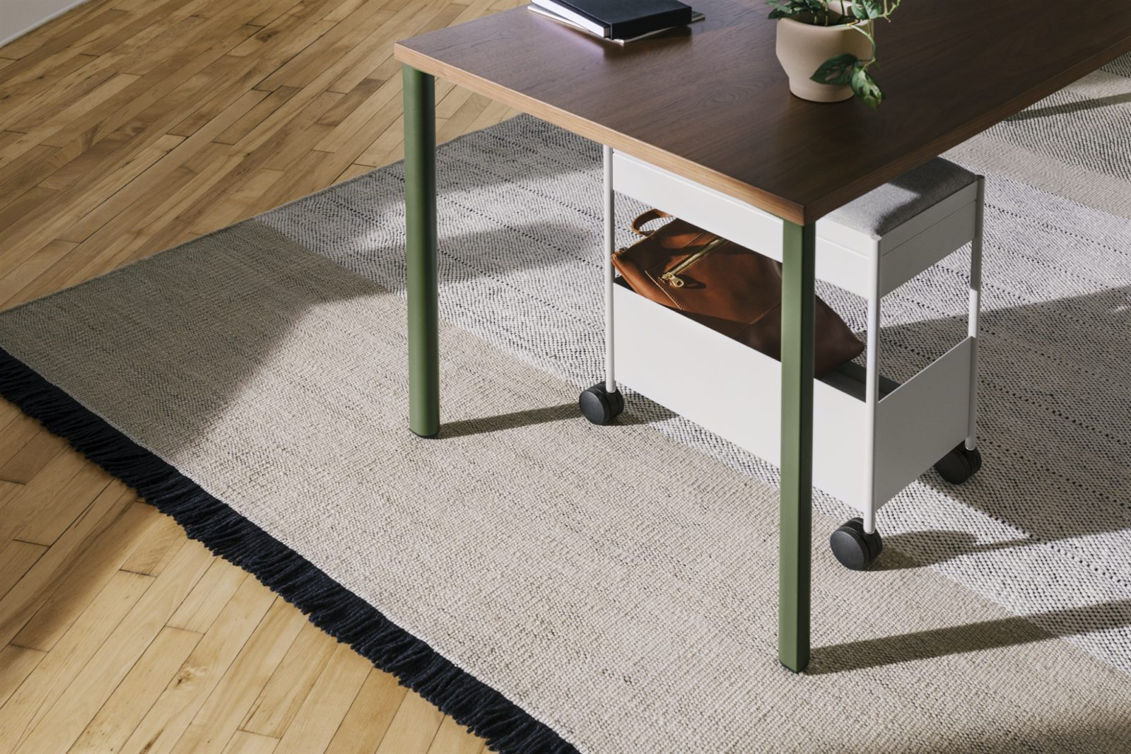 A white mobile individual OE1 Storage Trolley with a grey fabric cushion top and a large bottom shelf holding a purse positioned beneath a table.