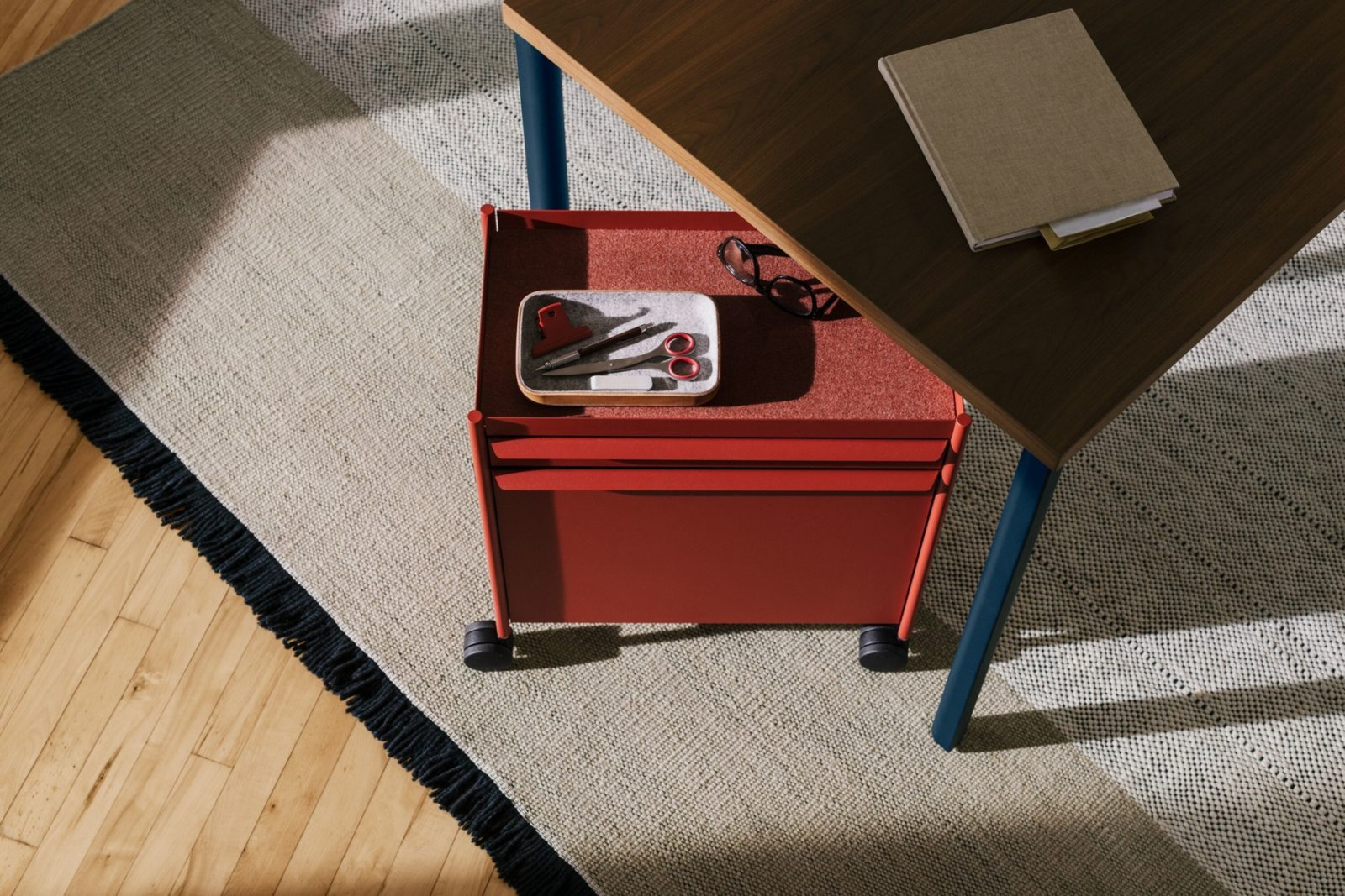 An individual red mobile OE1 Storage Trolley with a pencil tray on it's lined top beneath an OE1 Rectangular Table with a notebook on it.
