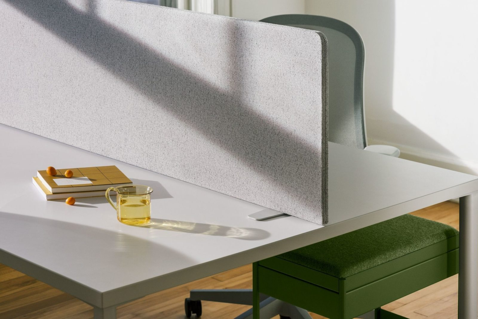 A green individual OE1 Storage Trolley with a cushion top beneath a table divided into two work spaces by a fabric OE1 screen.
