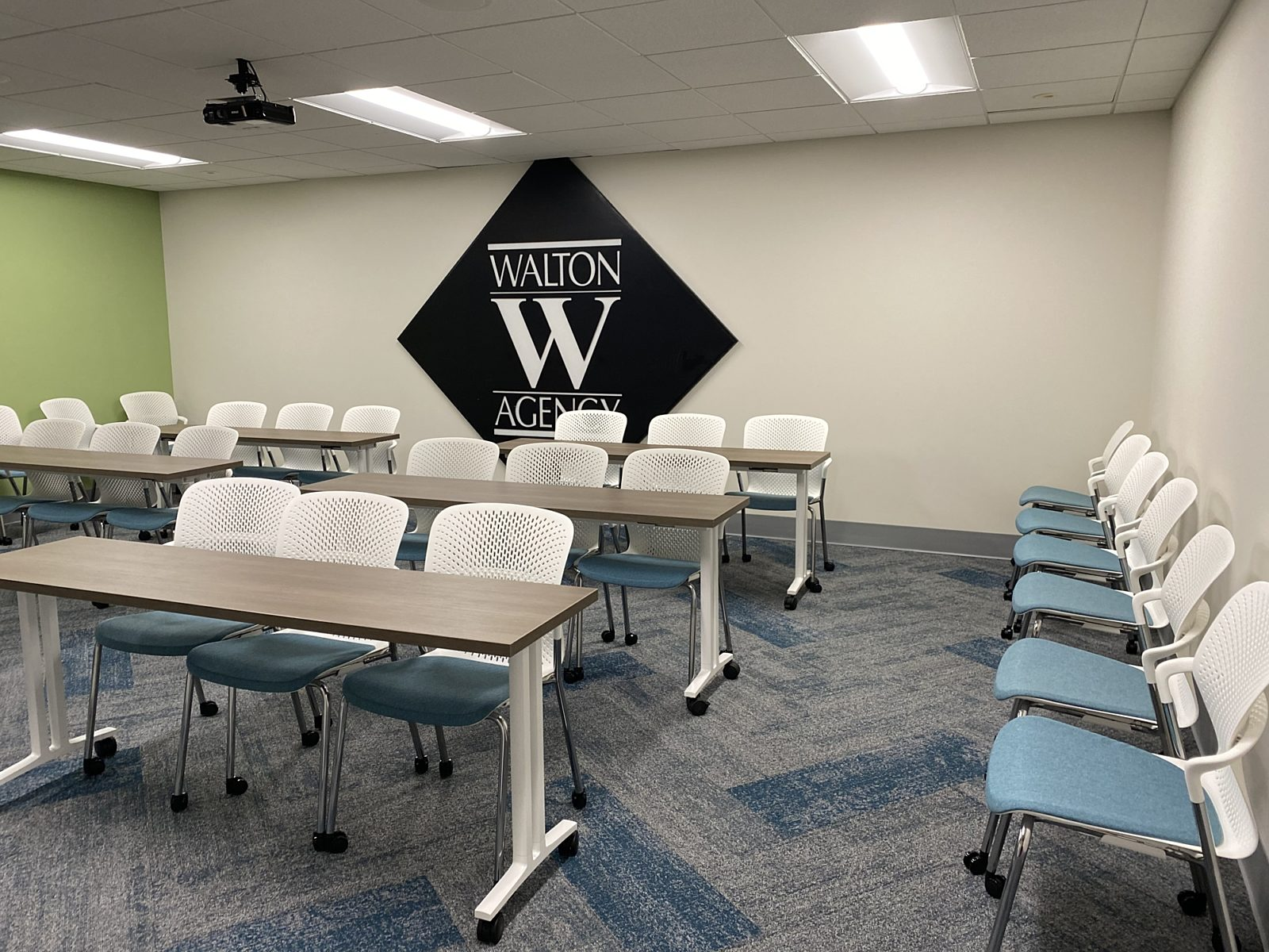 An image of a training room with mobile tables with wood tops, Caper chairs with blue seats and white shells arranged in rows in front of company logo.