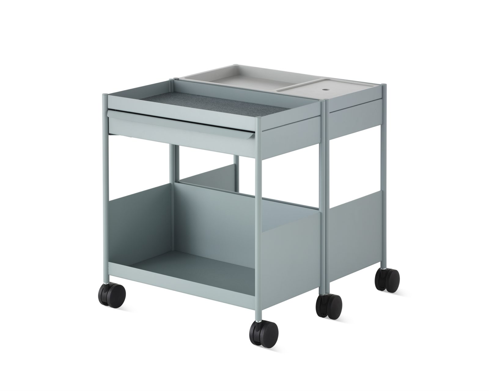 A light blue mobile duel OE1 Storage Trolley each with open tops, small top drawers, and open bottom shelves mirrored on both sides to serve two people.