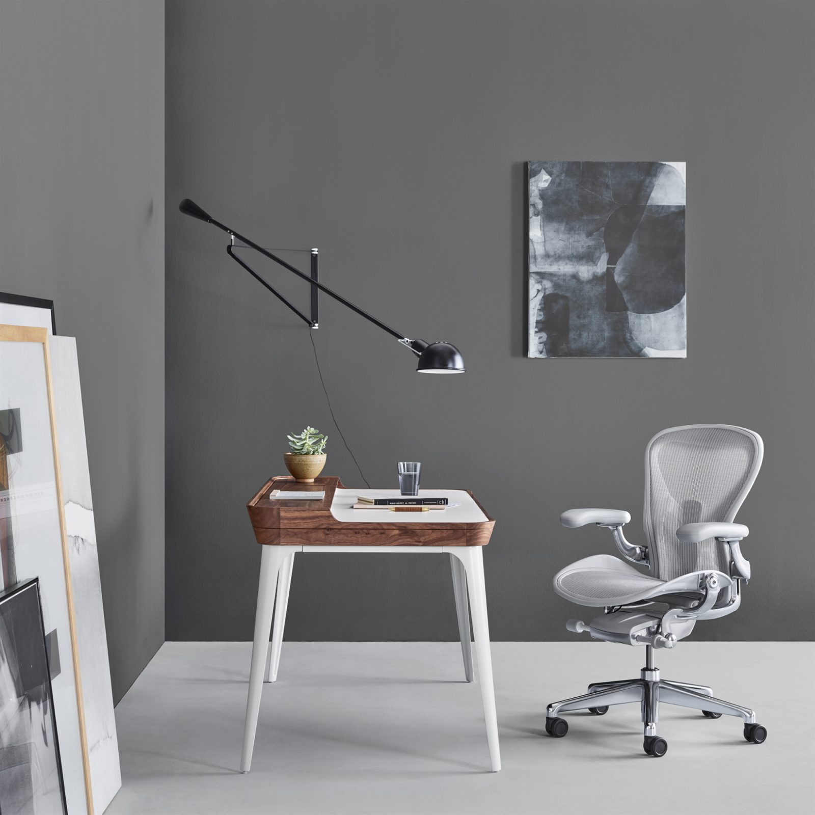 A home office with an Airea Desk in front of a mineral Aeron Chair with a black light fixture overhead.