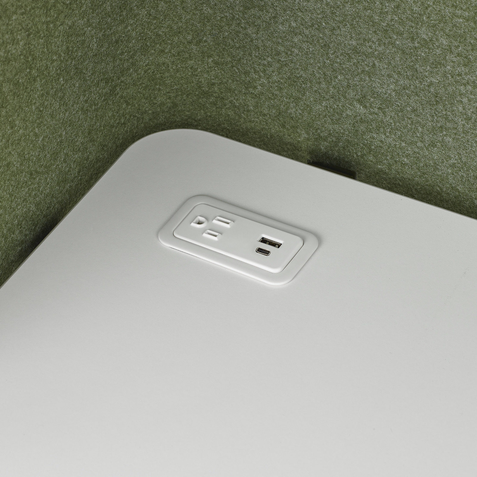 A close up image of an integrated surface power outlet with two usb ports and a simplex receptacle on a white work surface surrounded by a green screen.