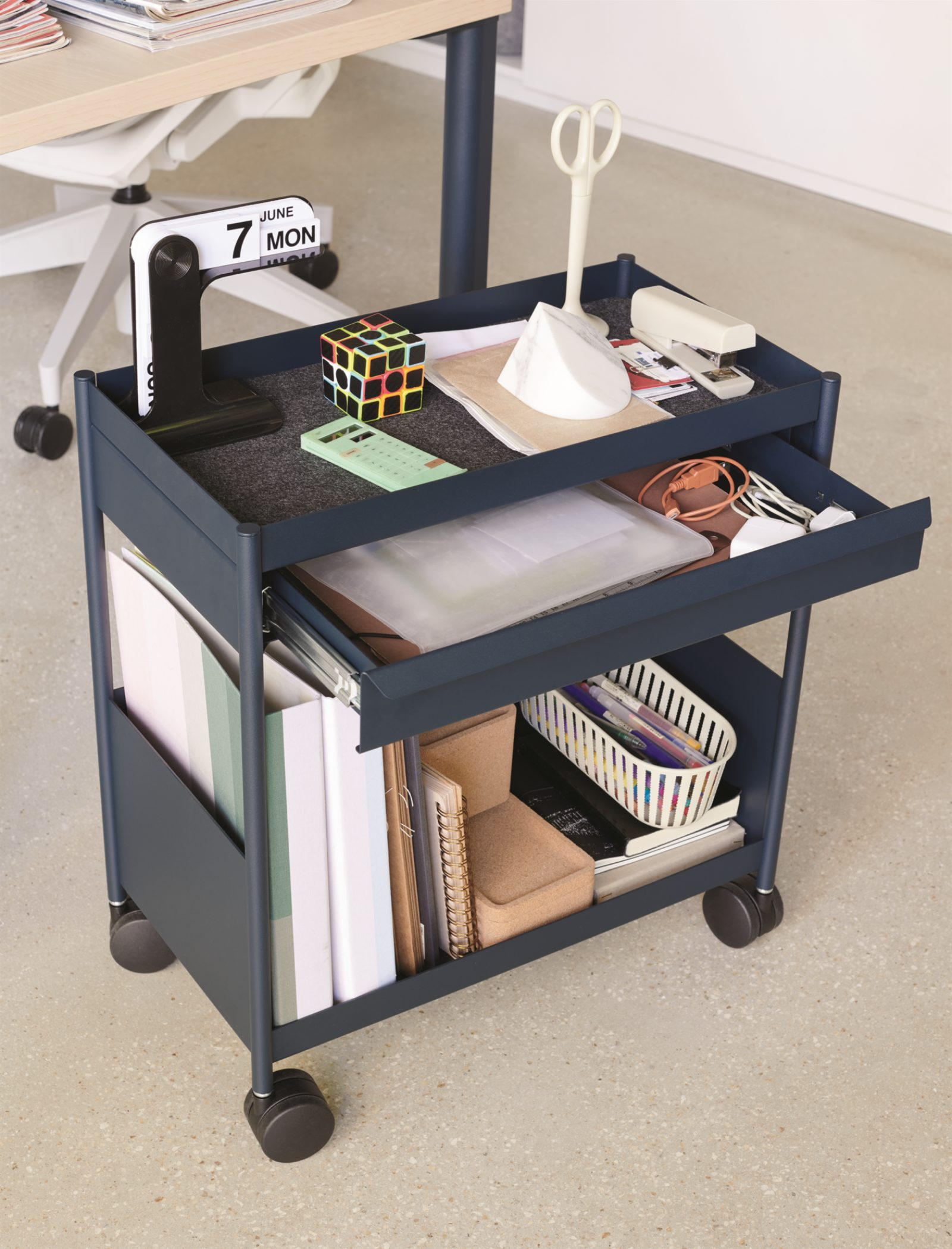 A navy individual OE1 Storage Trolley with the top filled with personal items, a pulled out drawer of papers, and binders and books on the bottom shelf.
