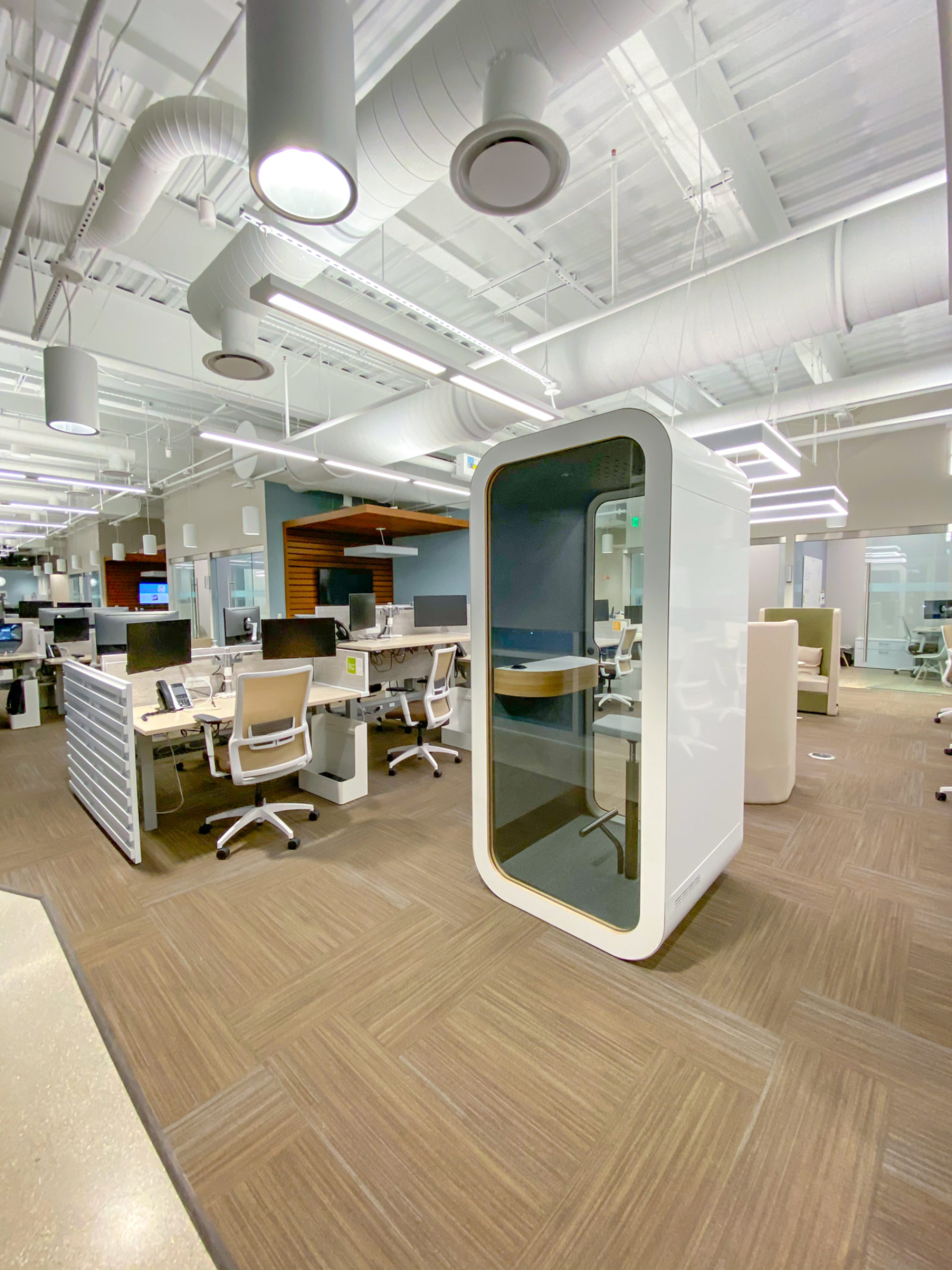 A white Framery O phonebooth in an open office plan with rows of workstations behind it.