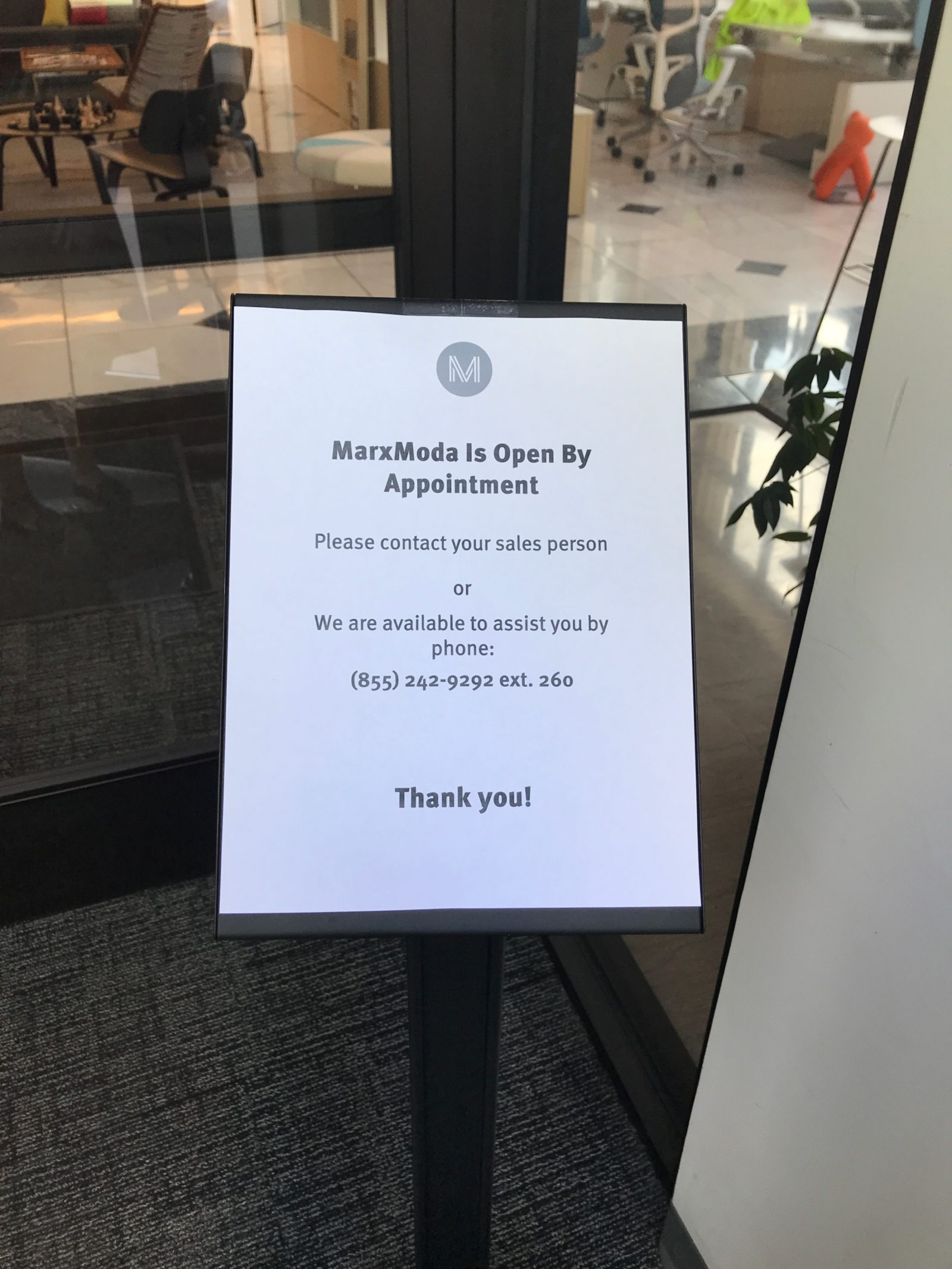 A sign informing visitors MarxModa is open for appointments.