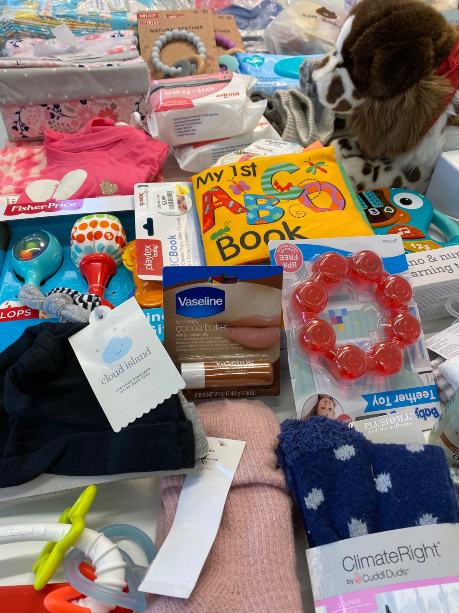 An image of a group of donated items including teethers, baby clothes, baby hats, and baby toys.