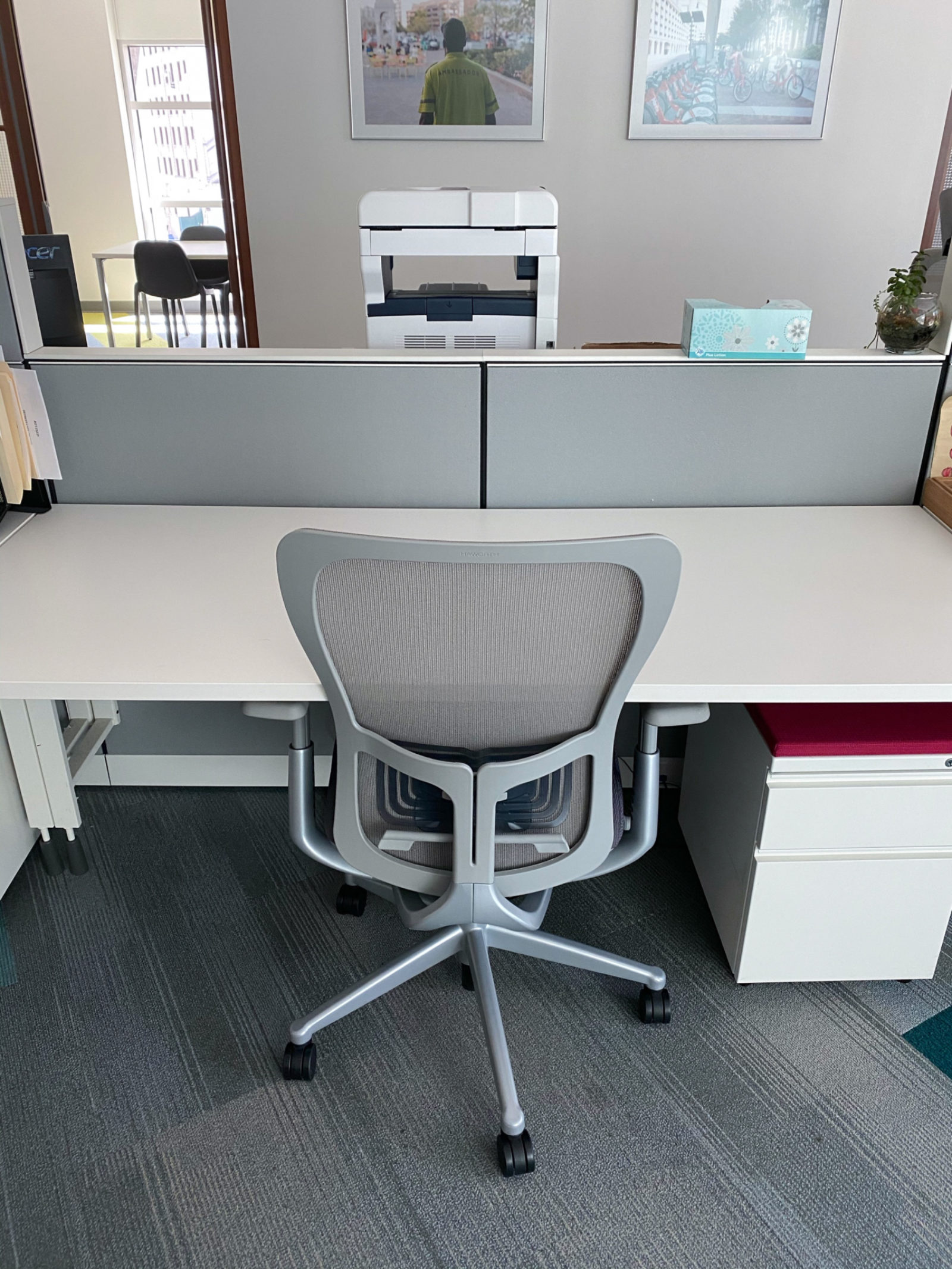 A picture of a workstation with a grey task chair in front of a white desk with grey panels and a white pedestal with a red top.