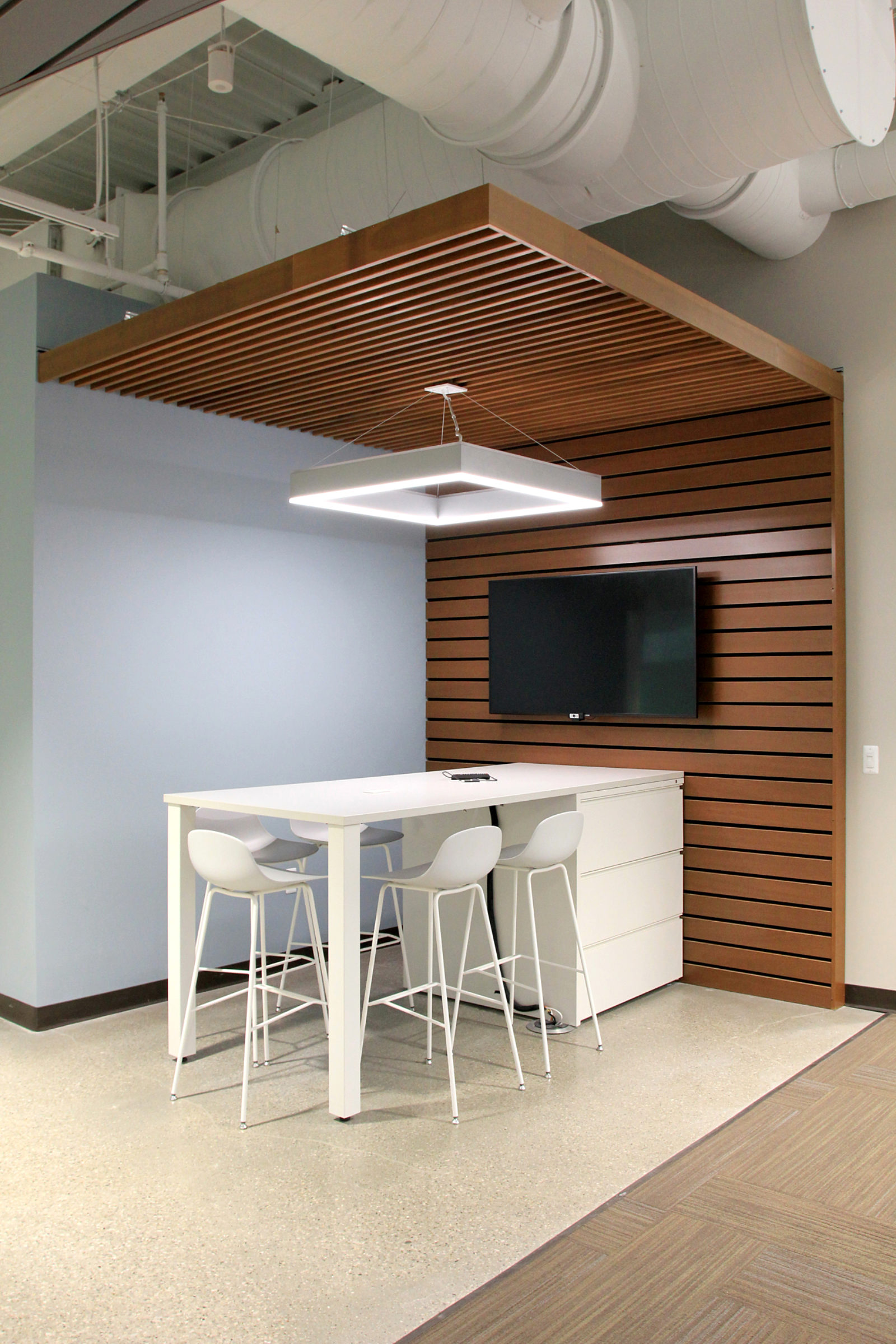 A long white countertop attached to a lateral file surrounded by white stools with a monitor mounted on a wood-paneled wall behind it.