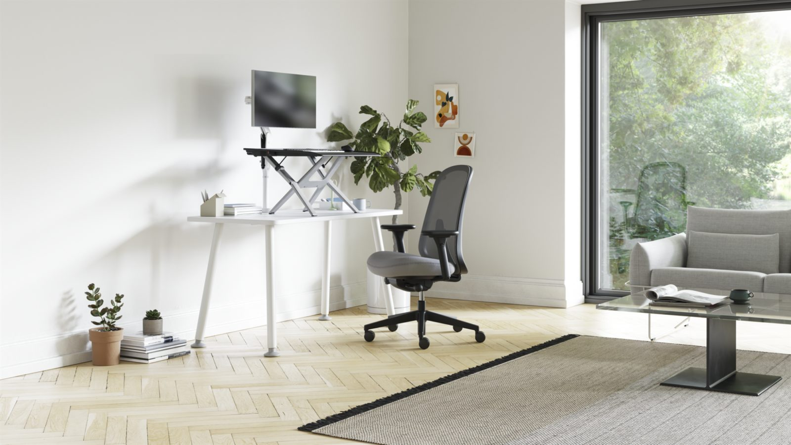 A home office with a Monto Sit-Stand Riser on a Memo Desk with a Verus Chair in front of it.