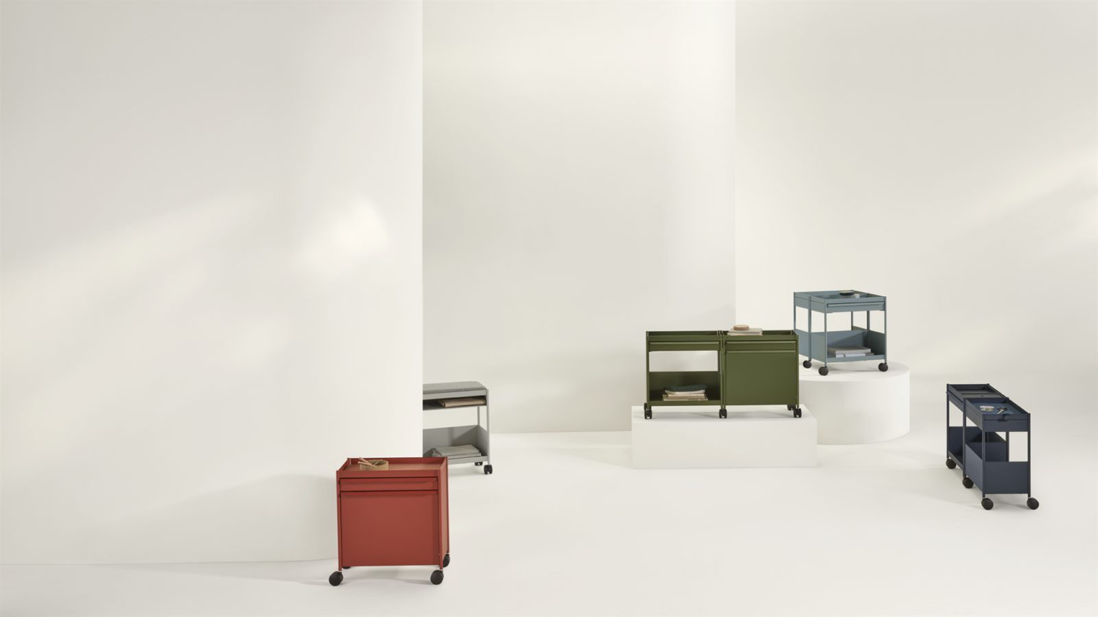 OE1 Storage Trolleys in different colors and configurations spread around a room with white walls, white columns, and a white floor.