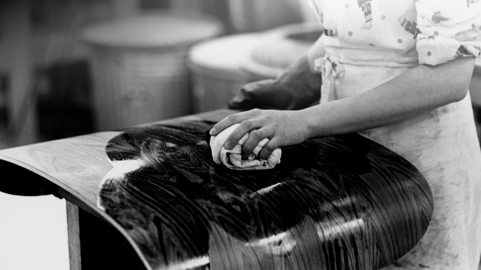 Image of someone cleaning the bottom of an Eames lounge chair.